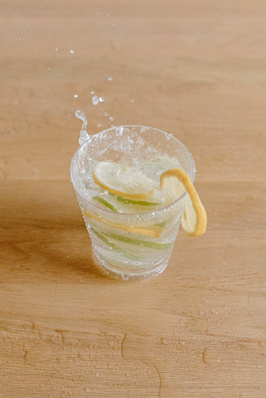 glass with refreshing drink decorated with lemon and lime slices